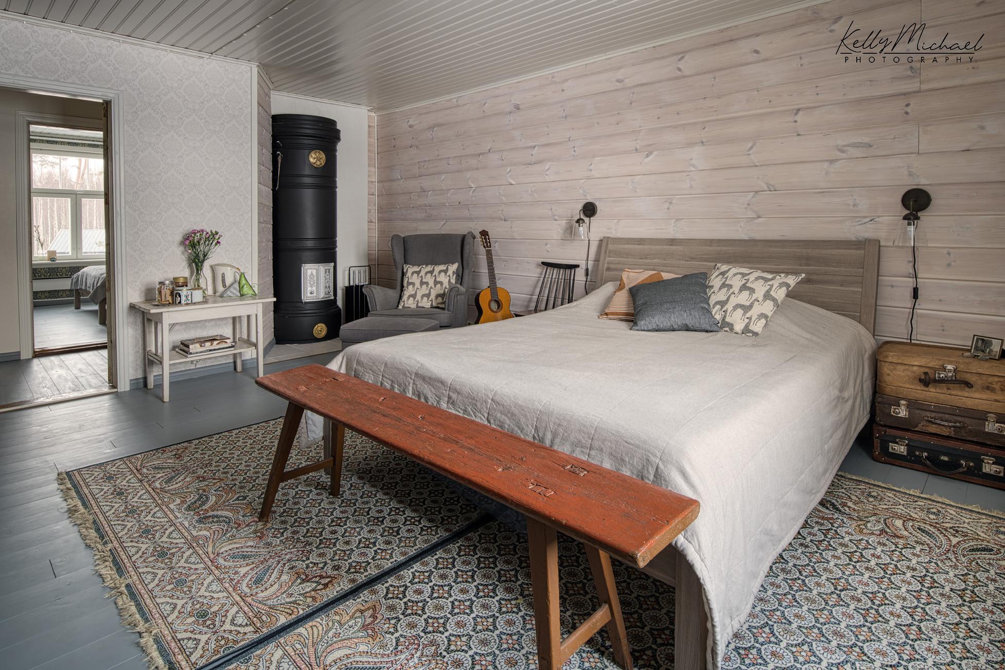 Vierashuone vaalea, sänky ja pönttöuuni